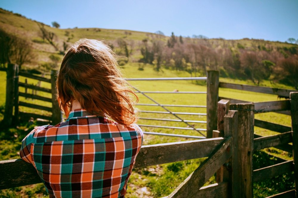 Young woman is standing by a fence on a ranch with cattle in the distance