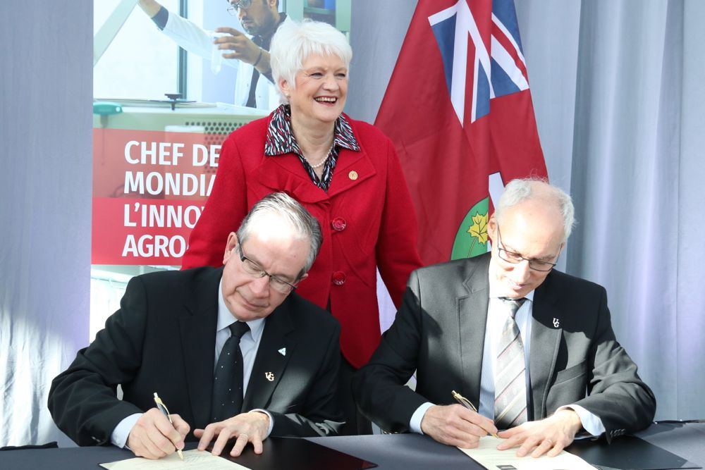 University of Guelph president Dr. Franco Vaccarino (right) and Ontario Agriculture Minister Jeff Leal sign a new research partnership agreement, with Guelph-area MPP Liz Sandals. (John Greig photo)