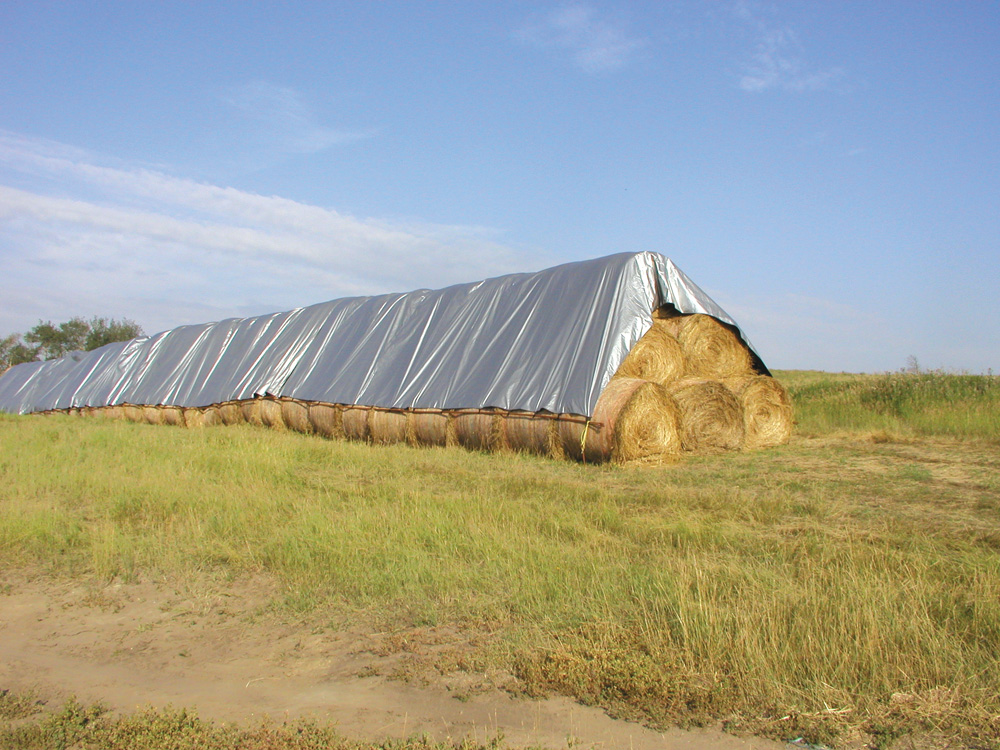 Round bales can be stored under tarps to keep out moisture and reduce rot.