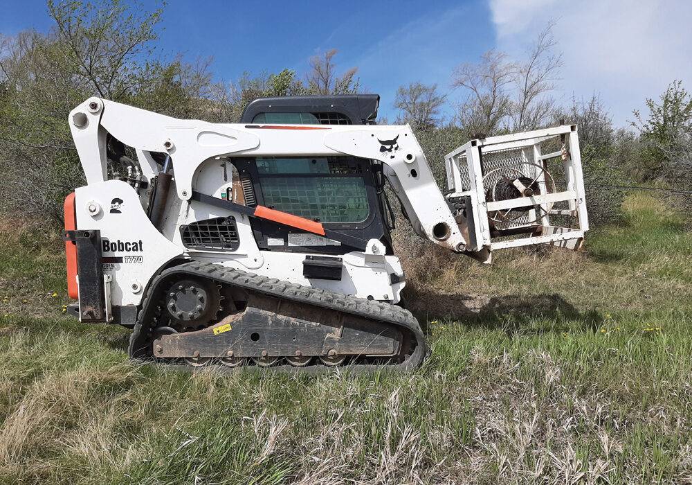 Todd Hermanson's Wire Shark mounts on a skid steer to ease the job of pulling and rolling wire.